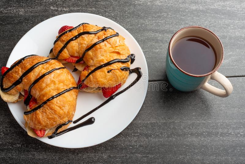 Fresh croissant on the table, with hot tea, strawberries and bananas, delicious breakfast stock photography