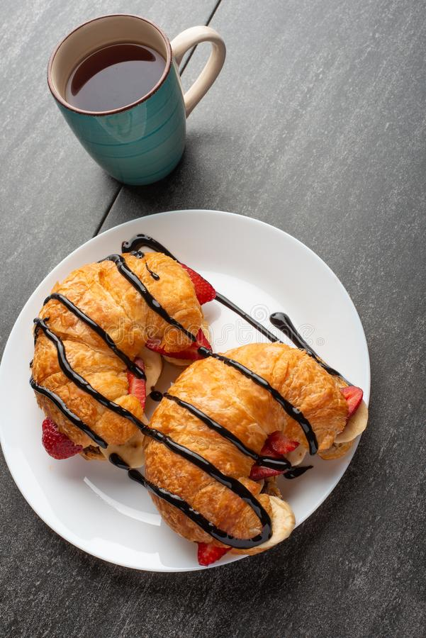 Fresh croissant on the table, with hot tea, strawberries and bananas, delicious breakfast.  royalty free stock image