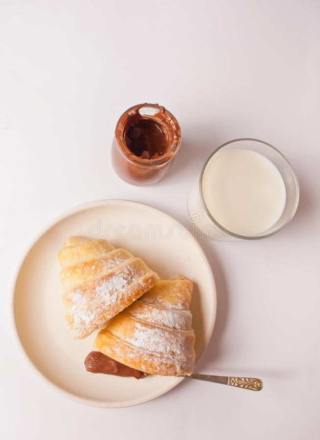 Fresh croissants bun with chocolate on the plate, glass of milk on the white background. Top view royalty free stock photography