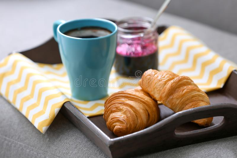 Fresh croissants, cup of coffee and jar with jam stock images