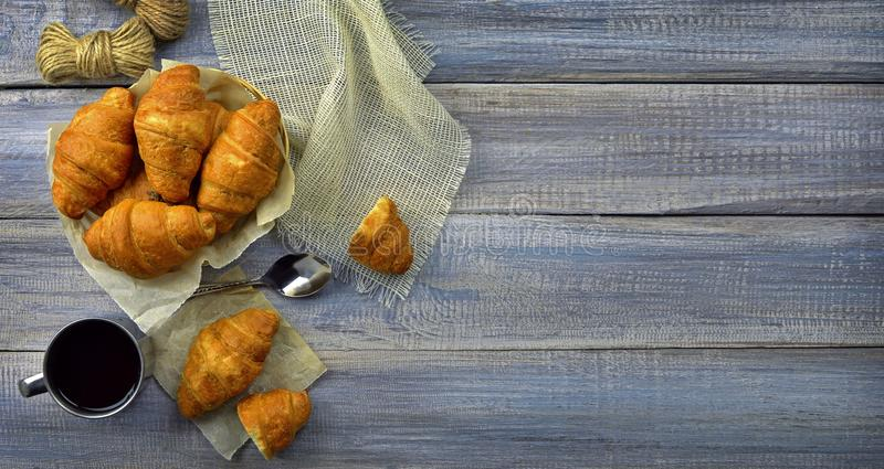 Fresh croissants and a cup of coffee / tea on an old wooden table. Breakfast. Top view. Homemade croissant served with black coffee or americano. Delicious stock photos