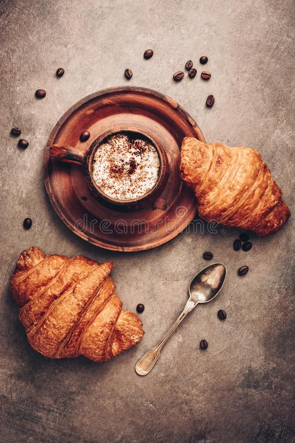 Fresh croissants and a cup of hot coffee on a dark brown rustic background. Top view, flat lay royalty free stock images
