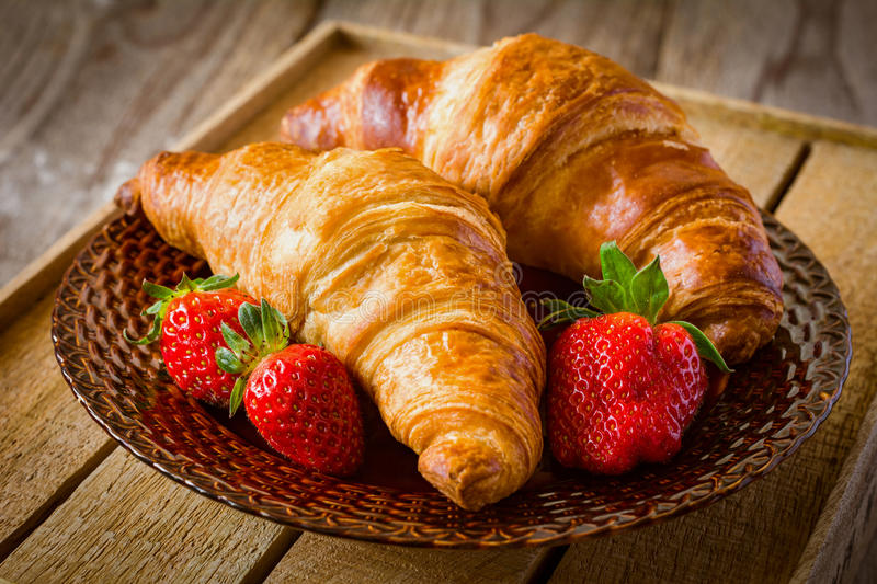 Fresh croissants with strawberries on plate, breakfast food, warm tone royalty free stock photography