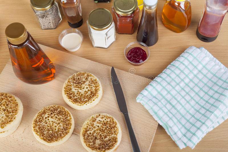 Fresh crumptes on a breakfast table with maple syrup. And many other condiments stock image