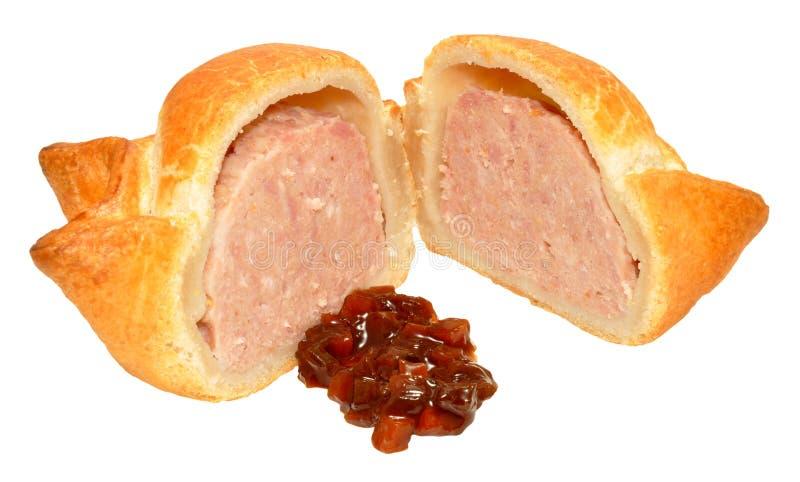 Fresh Crusty Pork Pie. A single fresh crusty pork pie cut in half with chutney relish isolated on a white background stock photography