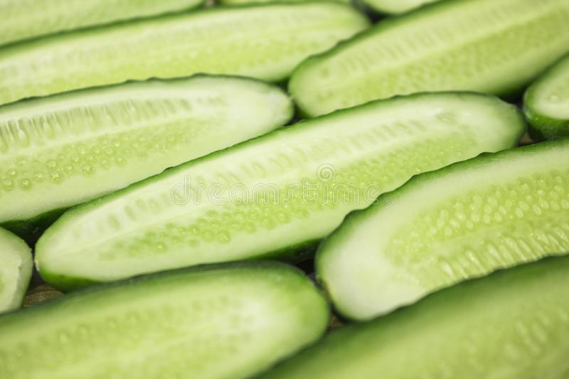 Fresh cucumber, chopped cucumber, isolated on wooden board. A pile of fresh picked cucumbers on wooden background. Halfed fresh cucumbers concept close up view stock photography