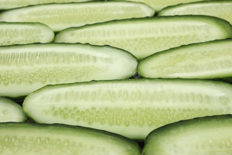 Fresh cucumber, chopped cucumber, isolated on wooden board. A pile of fresh picked cucumbers on wooden background. Halfed fresh cucumbers concept close up view royalty free stock photography