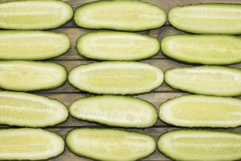 Fresh cucumber, chopped cucumber, isolated on wooden board. A pile of fresh picked cucumbers on wooden background. Halfed fresh cucumbers concept close up view stock photo
