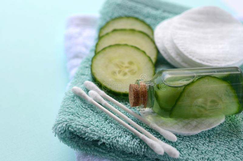 Fresh cucumber slices and natural beauty face toner in a glass bottle with copy space. SPA and beauty concept stock photo