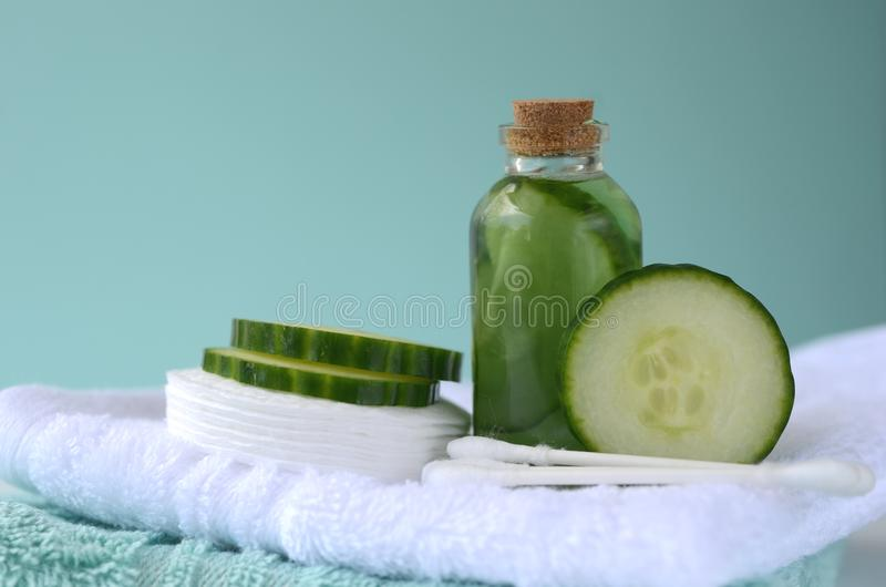 Fresh cucumber slices and natural beauty face toner in a glass bottle with copy space. SPA and beauty concept royalty free stock photography