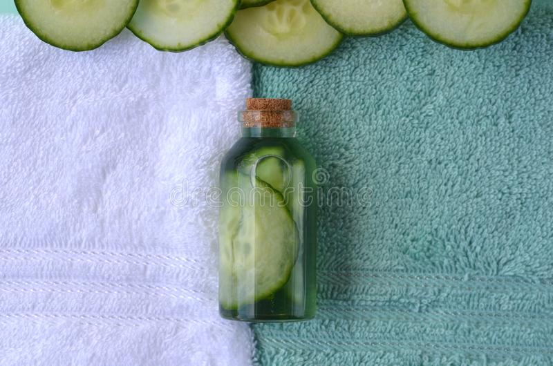 Fresh cucumber slices and natural beauty face toner in a glass bottle with copy space. SPA and beauty concept royalty free stock photos