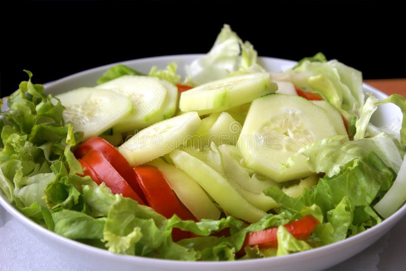 Fresh cucumber and tomato salad. Fresh cucumber, tomato and lettuce salad in white plate on wood table with napkin and black background royalty free stock image