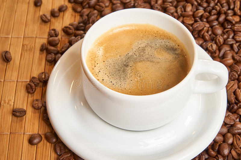 Fresh cup of coffee surrounded by coffee beans on a wooden background stock photos