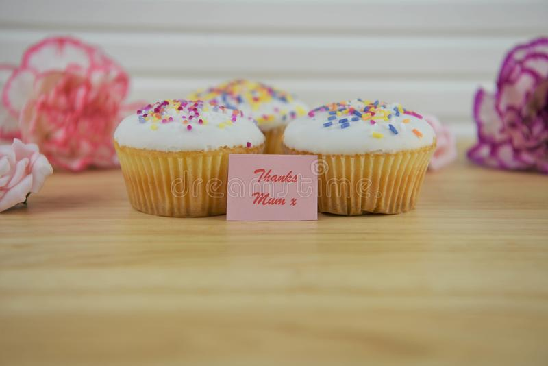 Fresh cupcakes with flowers and a mothers day note of thanks royalty free stock photo