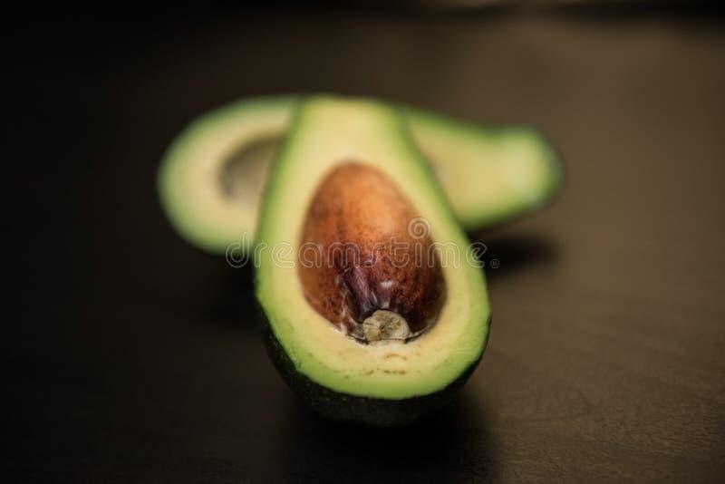 Fresh avocado on dark background. Vegetarian food concept. Top view. royalty free stock photo