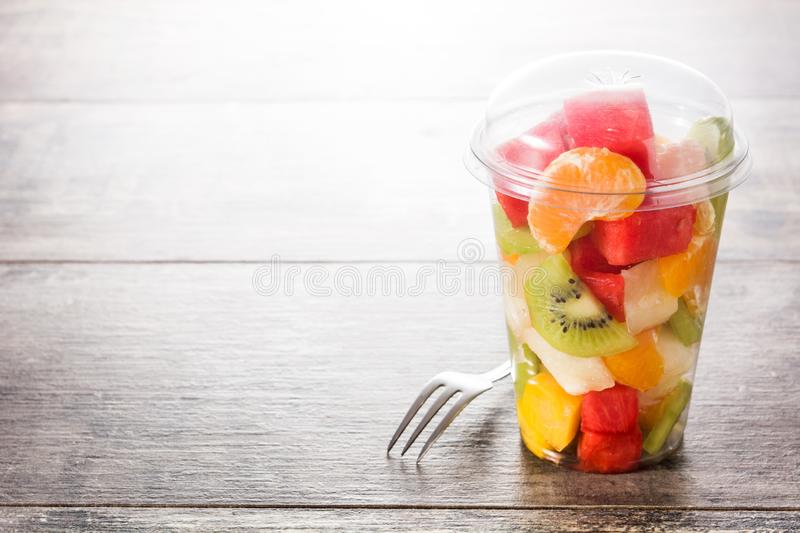 Fresh cut fruit in a plastic cup on wood royalty free stock photography