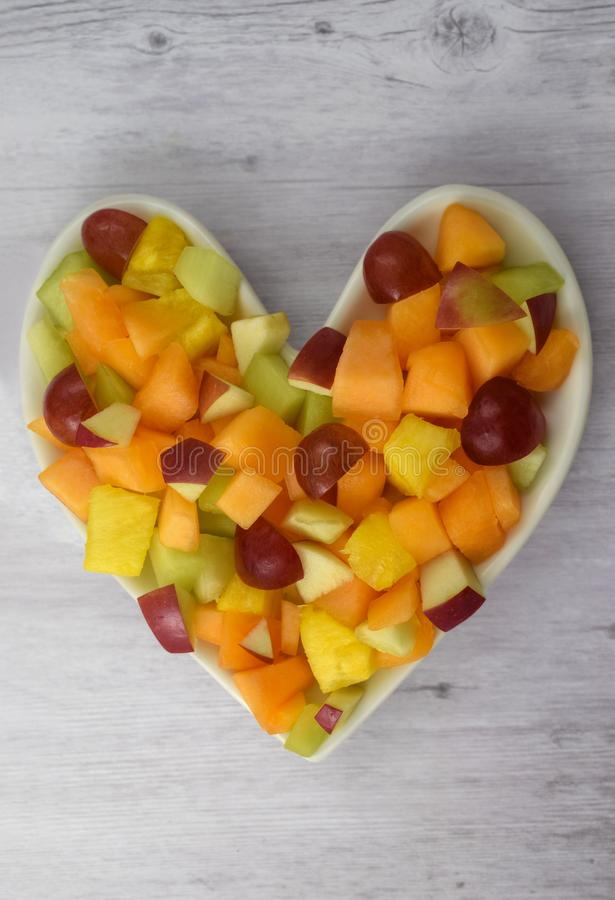 Heart Healthy Fruit Salad with Grapes, Pineapple, Apples, Canteloupe and Honeydew Melons. Atop weathered gray wood background. royalty free stock images