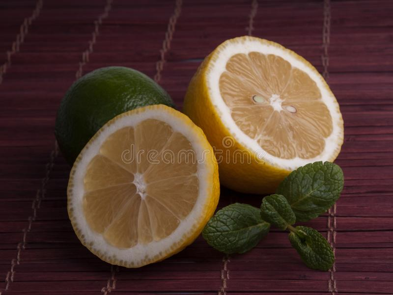 Fresh cut lemon and lime with mint. On bamboo napkin royalty free stock image