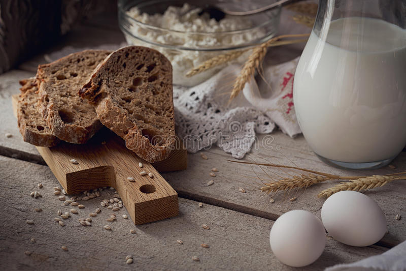 Fresh dairy products. Milk, cottage cheese, sour cream, multigrain homemade bread, fresh eggs and wheat on wooden background. royalty free stock image