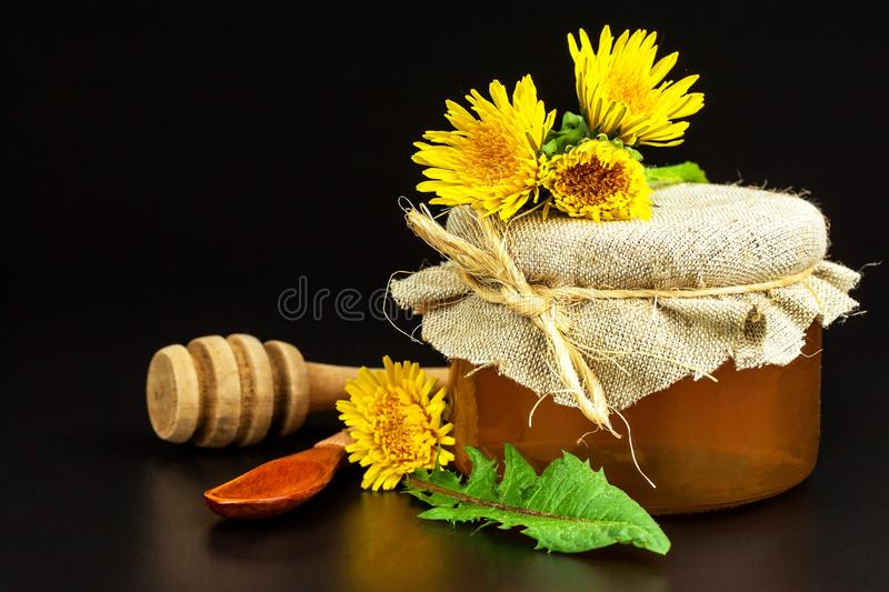 Fresh dandelion honey in a glass. Honey production of dandelions. On a black background. royalty free stock photo