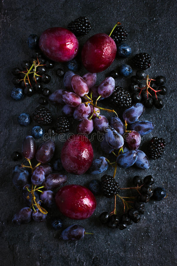 Fresh dark fruits and berries on black background. Top view royalty free stock photos