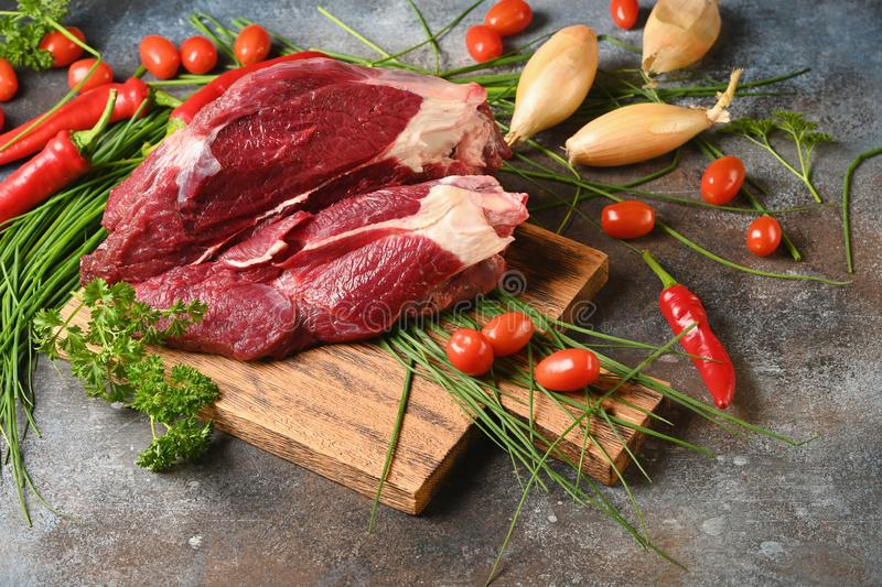 Fresh dark meat with ingredients for cooking on brown wooden cutting board. royalty free stock photos
