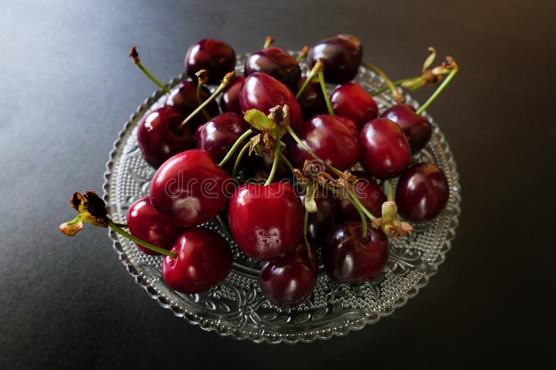 Fresh Dark Red Cherries in a Transparent Plate isolated on a Black Background royalty free stock photo