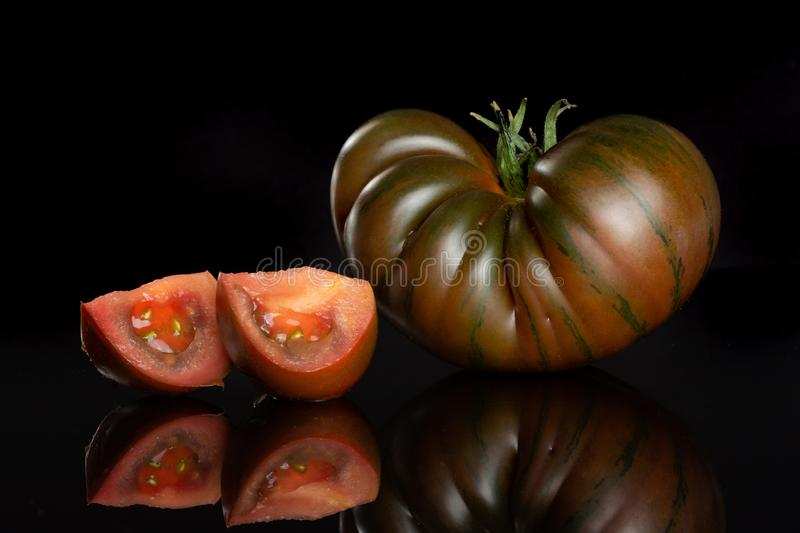 Fresh dark tomato primora isolated on black glass. Group of one whole two slices of fresh tomato primora isolated on black glass royalty free stock images