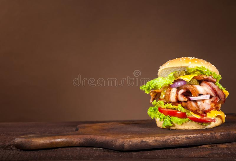 Fresh delicious big burger on a wooden background stock photography