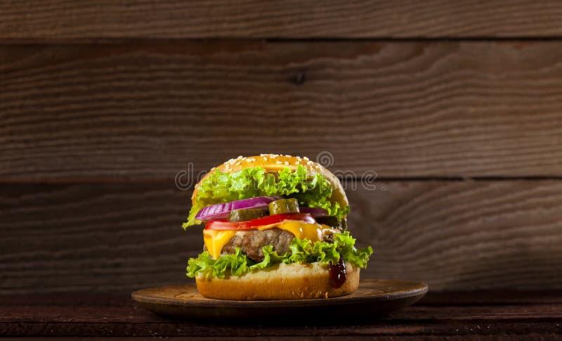 Fresh delicious big burger on a wooden background stock photos