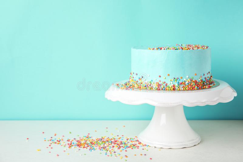 Fresh delicious birthday cake on stand against color background. Space for text royalty free stock photography