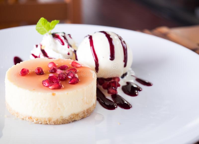 Fresh delicious cheesecake with vanilla ice-cream, berries sauce royalty free stock photography