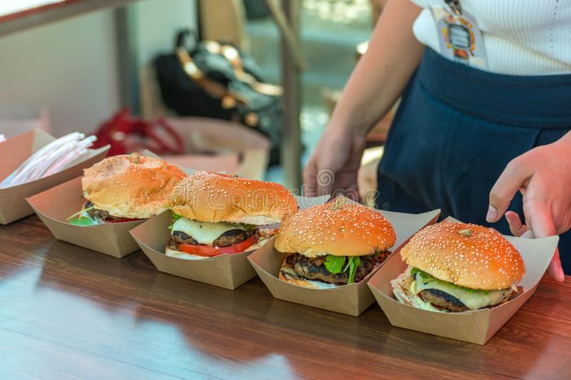 Fresh delicious grilled burgers on wooden table. Street food festival.  stock photography