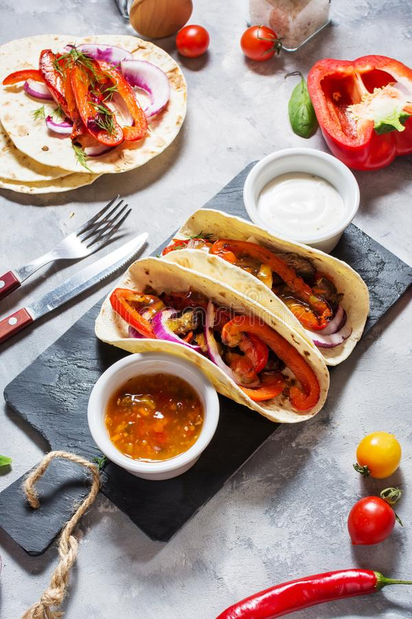 Fresh delicious mexican tacos and food ingredients on concrete background. Fresh delicious mexican tacos and food ingredients on concrete background royalty free stock photography