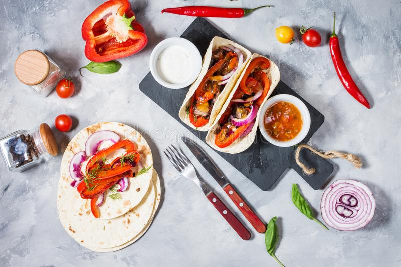 Fresh delicious mexican tacos and food ingredients on concrete background. Top view stock photography