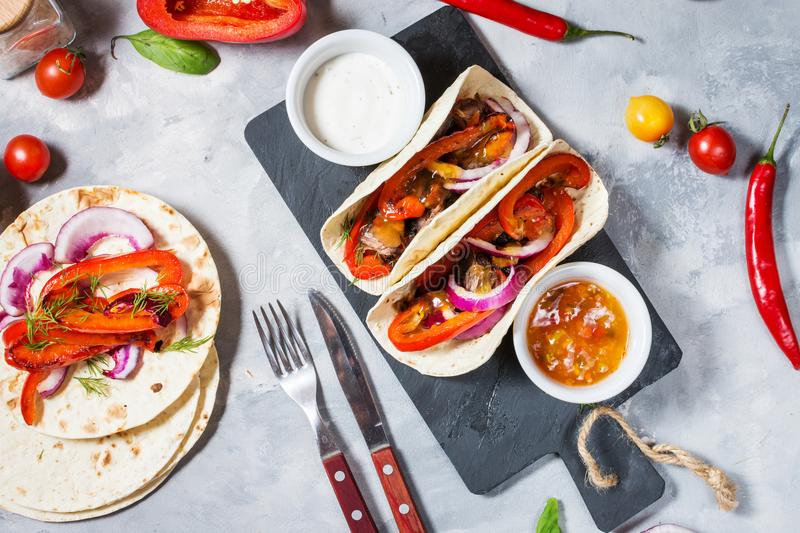 Fresh delicious mexican tacos and food ingredients on concrete background. Top view royalty free stock photo