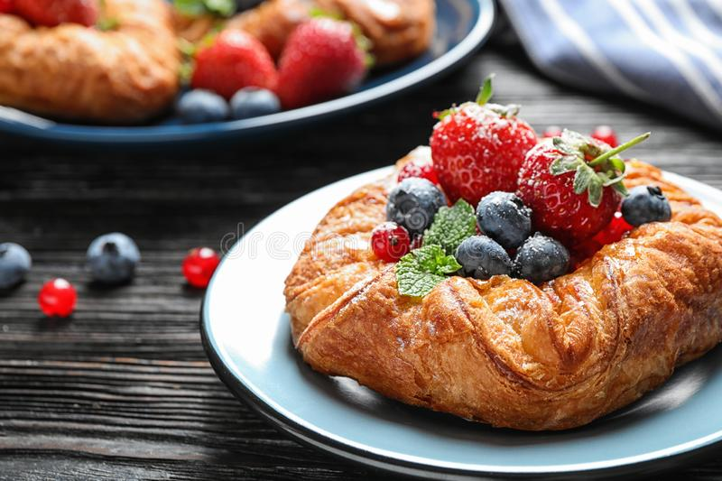 Fresh delicious puff pastry with sweet berries on dark wooden. Table stock photography