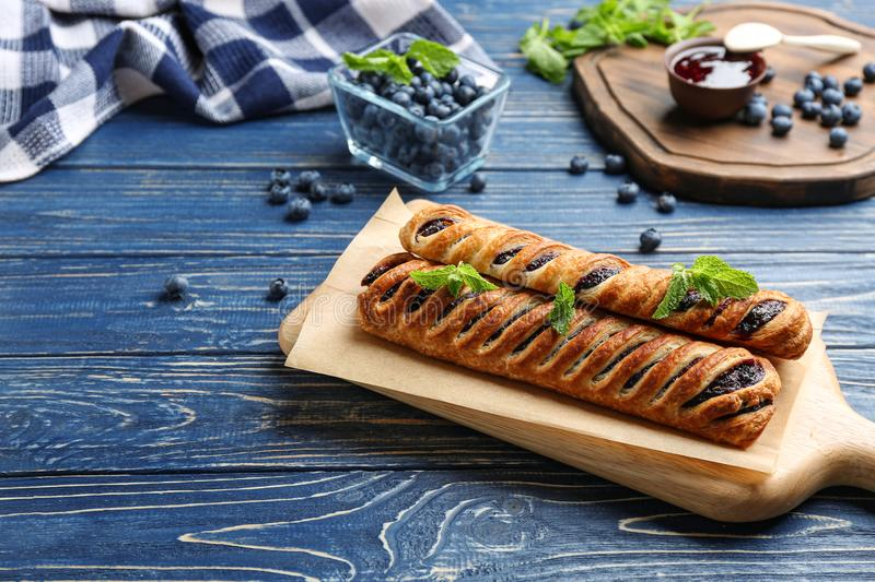 Fresh delicious puff pastry with sweet  served on blue wooden table. Fresh delicious puff pastry with sweet berries served on blue wooden table royalty free stock photos