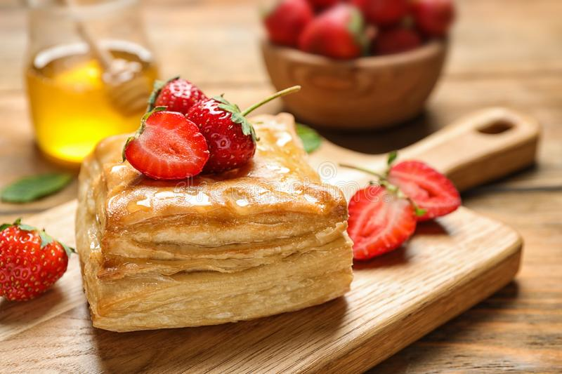 Fresh delicious puff pastry with sweet strawberries on wooden table. Closeup stock photo