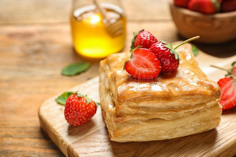 Fresh delicious puff pastry with sweet strawberries on wooden table, closeup. Space for. Text royalty free stock photos