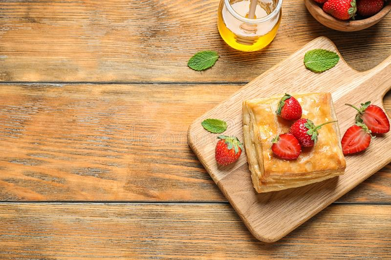 Fresh delicious puff pastry with sweet strawberries on wooden table, flat lay. Space for. Text royalty free stock images