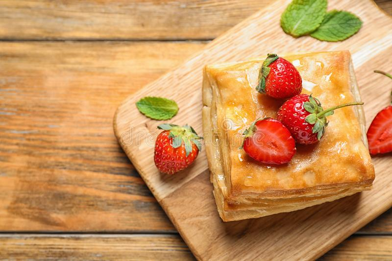 Fresh delicious puff pastry with sweet strawberries on  table, top view. Space for text. Fresh delicious puff pastry with sweet strawberries on wooden table, top stock images