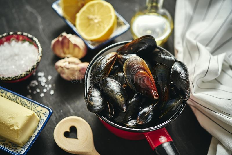 Fresh, delicious raw mussels in a saucepan with butter, garlic, parsley, lemon stock photos