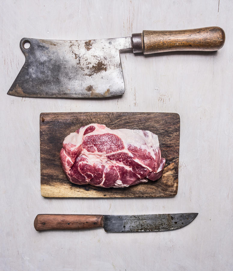 Fresh, delicious raw pork steak on a cutting board with a meat cleaver and a knife wooden rustic background top view close up. Fresh, delicious raw pork steak on royalty free stock photos