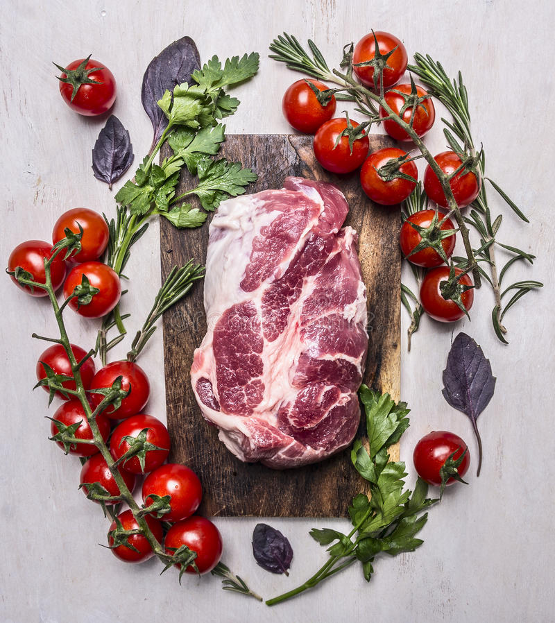 Fresh, delicious raw pork steak on a cutting board with vegetables, herbs wooden rustic background top view close up stock photography