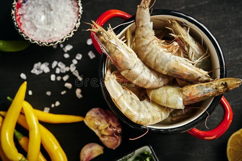 Fresh delicious raw tiger prawns in a pot with parsley, lemon, butter, tomatoes and chili peppers royalty free stock photos