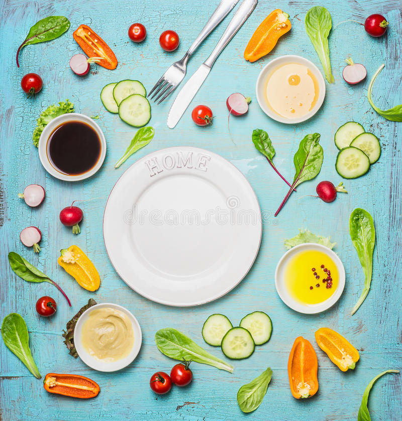 Fresh delicious salad and dressing ingredients around empty white plate on light blue background, top view, frame. Health salad ma. King. Flat lay of healthy stock image
