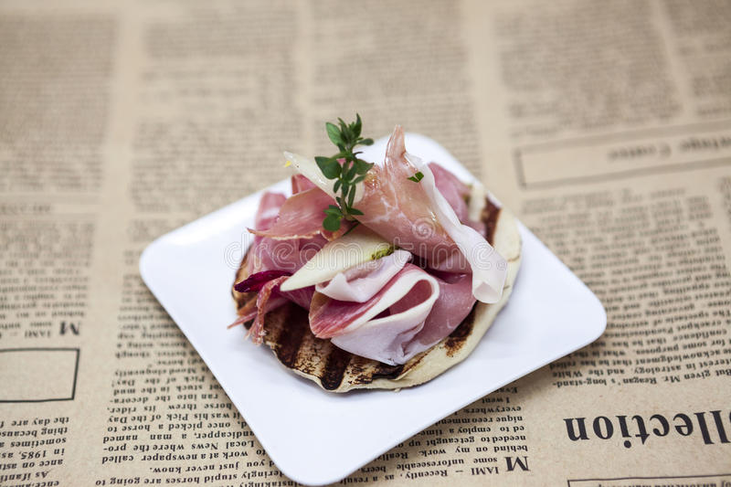 Fresh delicious Spanish tapas with hamon on the background of newspapers. Great background for restaurant, cafe.  royalty free stock image