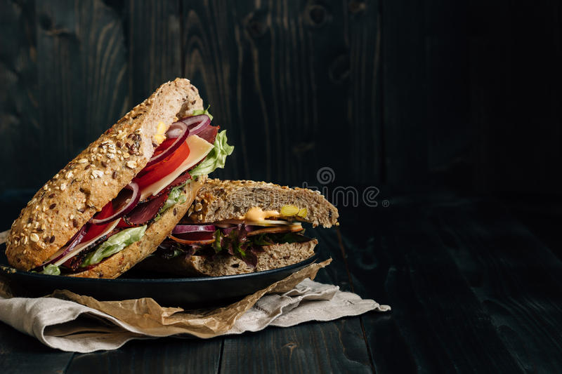 Fresh delicious submarine sandwich on the wooden dark table, with copy space stock images