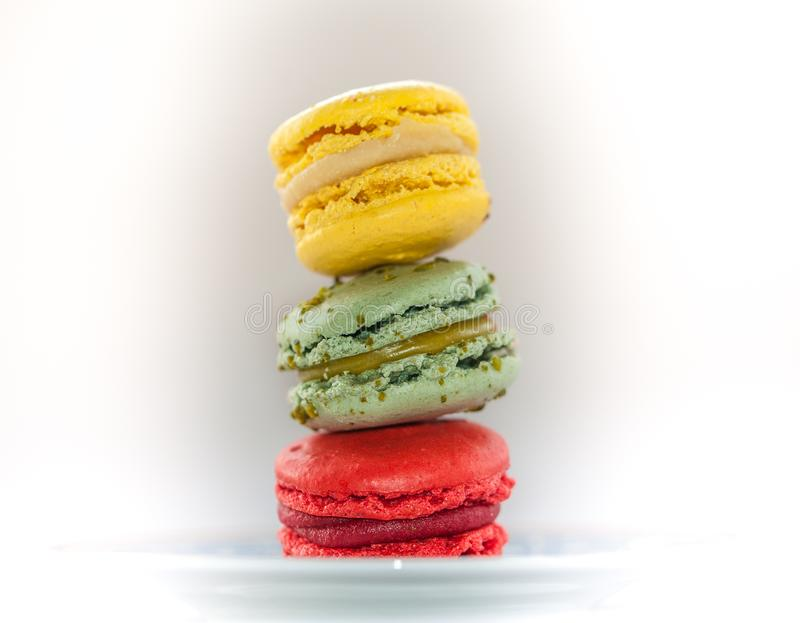 Colourful macarons on a plate with blue pattern stock photos